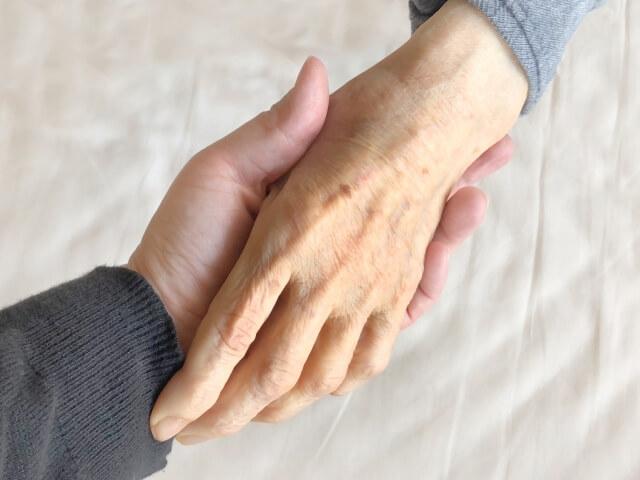 おばあちゃんの手を握る娘