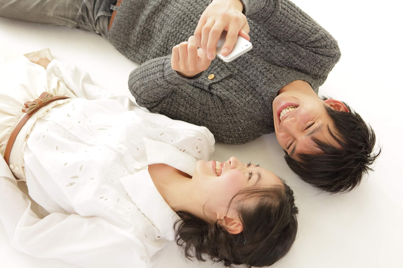 爽やかな男性が彼女と寝そべって笑顔でスマホゲームをしている