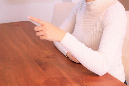 指を指して相手の間違いを指摘する女性