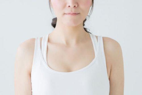 ほっぺたを膨らましている白いタンクトップ姿の女性