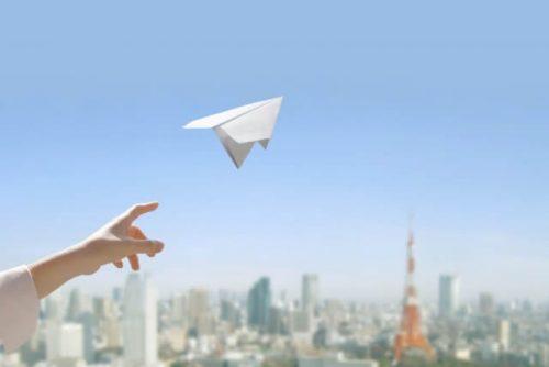 紙飛行機を空に向かって飛ばす