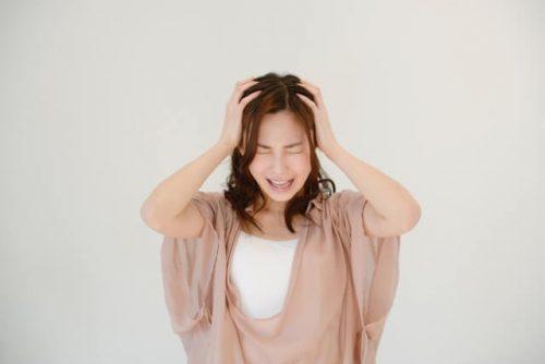 頭を掻き毟って発狂する女性