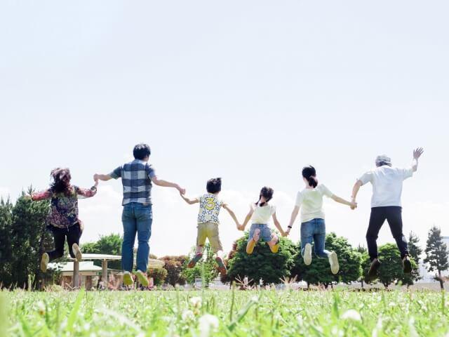 公園で仲良く手をつないでジャンプする家族