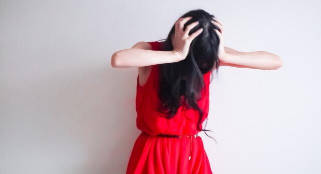 彼氏との付き合いにうんざりして髪を掻き毟っている女性