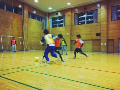 学校の体育時間でフットサルをする学生