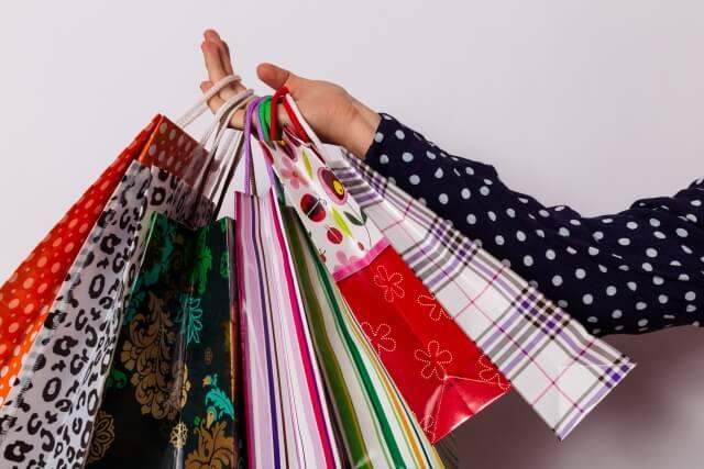 待ちに待った収入で散財して買い物袋を大量にもった主婦