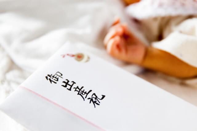 出産祝い金の近くで眠る赤ちゃん