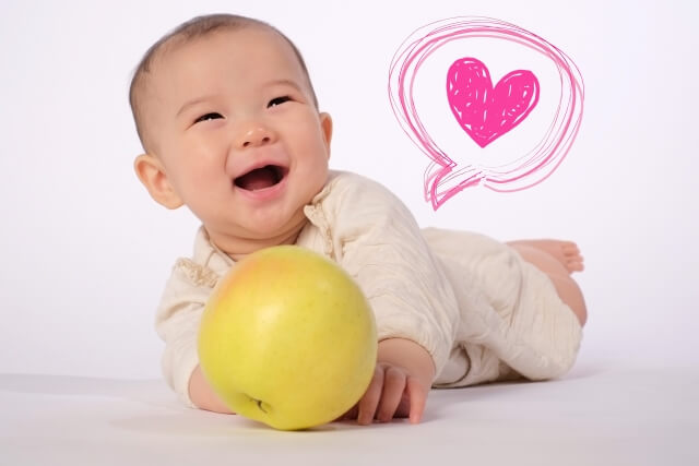 りんごを転がして遊んでいる笑顔の赤ちゃん