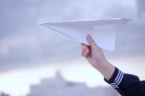 紙飛行機を飛ばしている女子高生