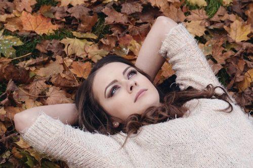 公園で枯葉の上で寝そべっている女性