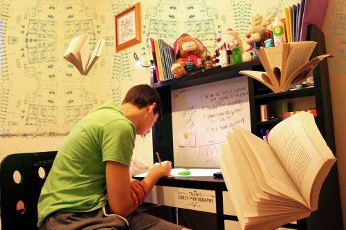 机に向かって必死に勉強をする男性