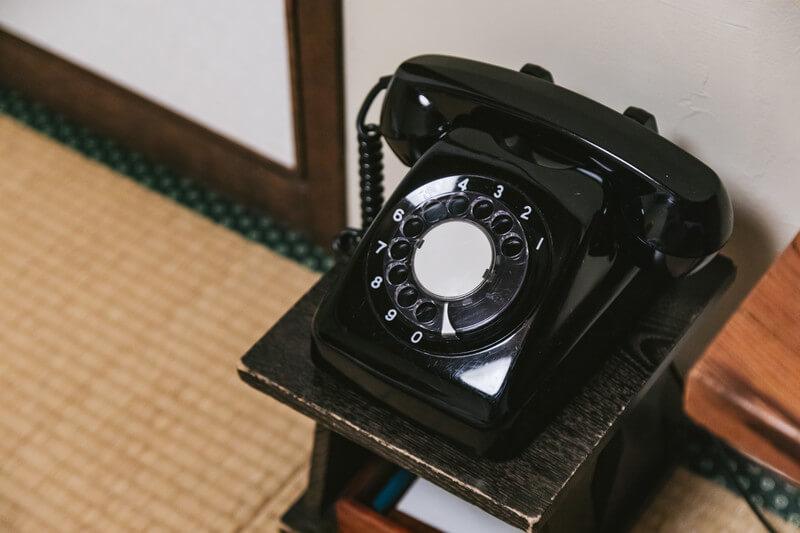 不満のある状況を変えたくて黒電話の前で面接の電話をかけようか迷っている