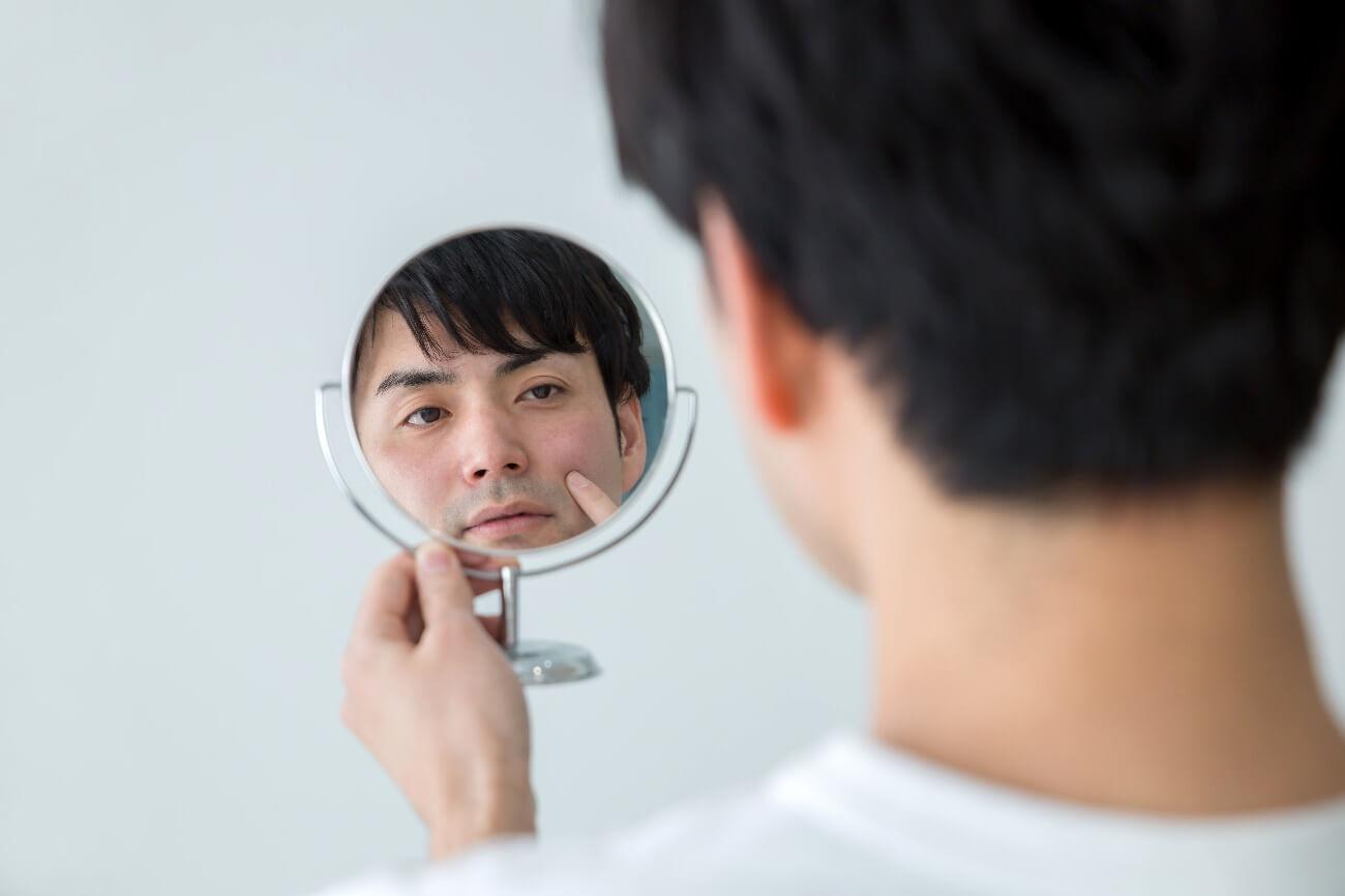 手鏡で自分の顔を眺める男性