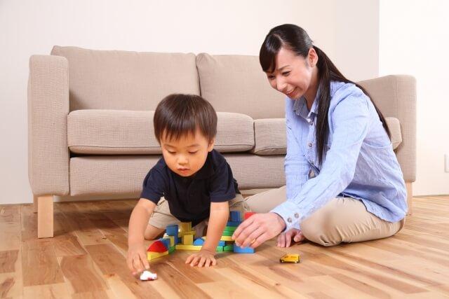 気を使いつつ上司の子供と一緒に遊んでいる女性