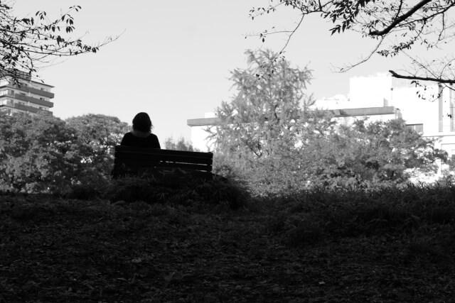 配偶者に先立たれて公園で打ちひしがれている人