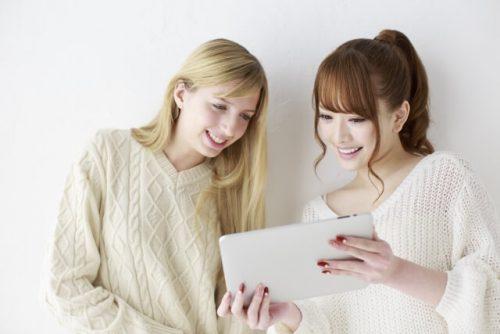 留学先で仲良くタブレットを見る女性二人