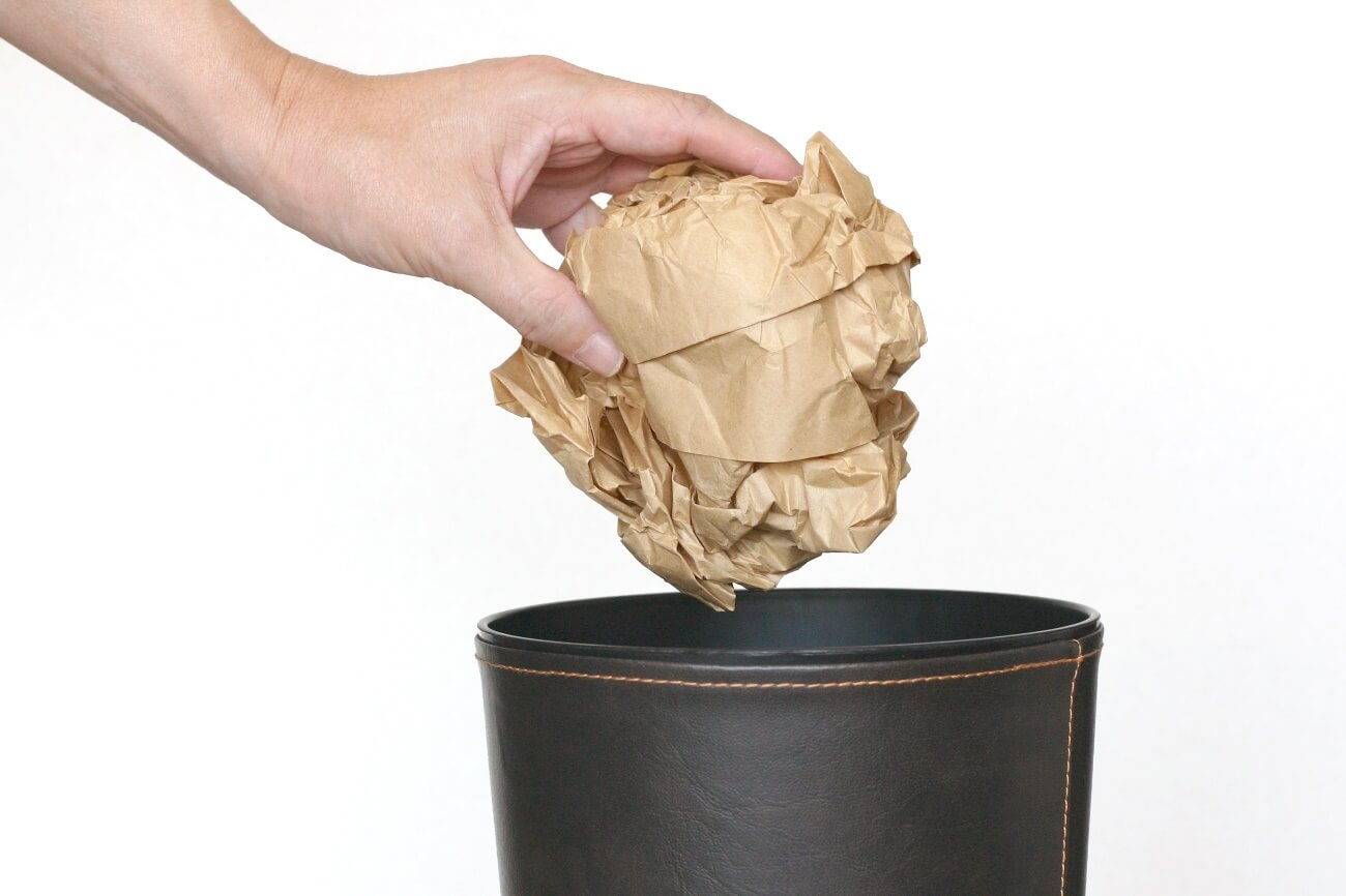 大きな紙クズをゴミ箱に捨てている