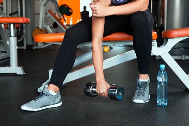 体型を維持するためにジムで腕を鍛えている女性