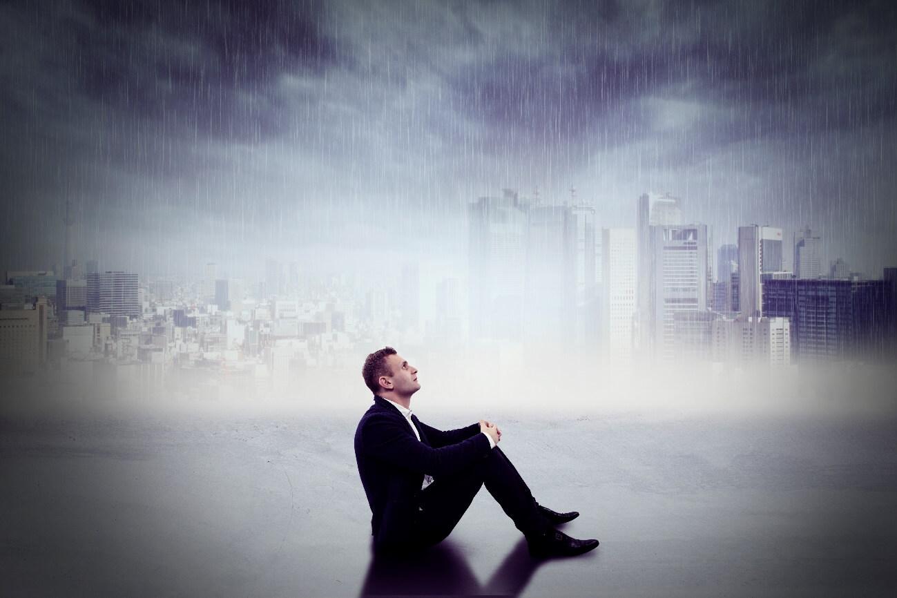 老後の不安を胸に募らせてぼんやり空を眺めている男性