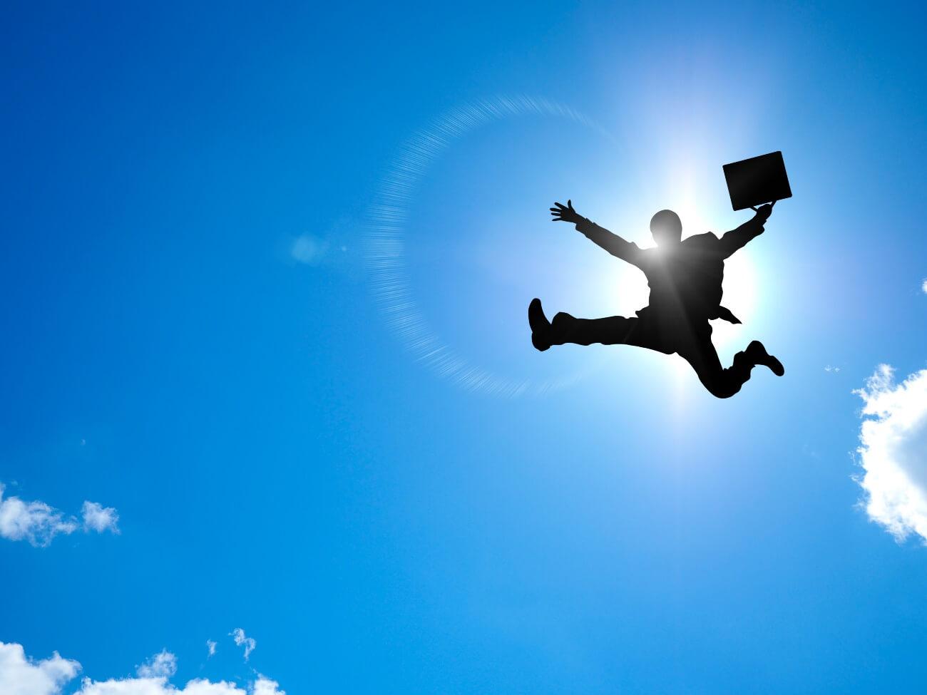 空に向かって全身を広げてジャンプしているサラリーマン