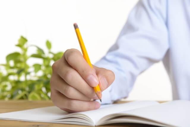 ノートに遺書を書く男性