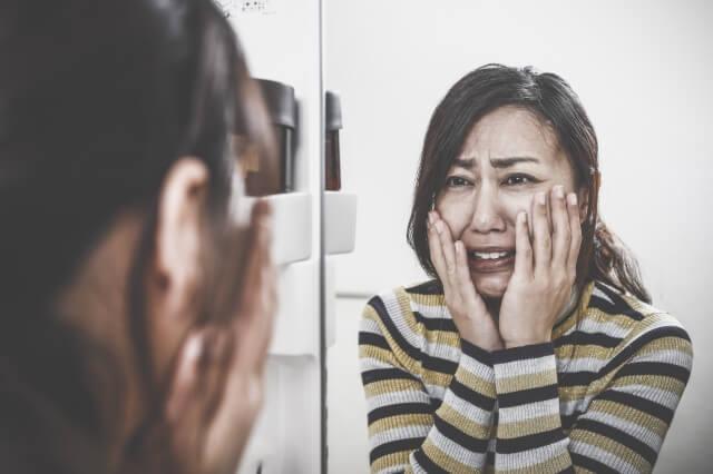 鏡を見て自分の顔の大きさを気にしている女性