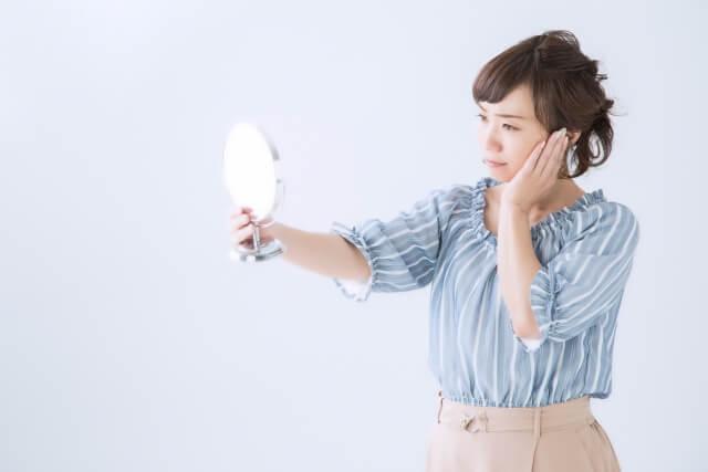手鏡でみて顔の横幅が大きいんじゃないかと気にしている女性