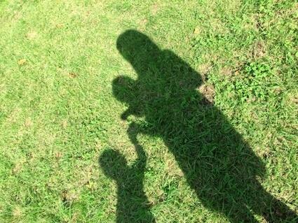公園で小学生と手をつなぎ、赤ちゃんを抱っこしている母親