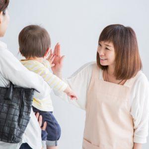 保育所で子どもとお別れの時にタッチしている保育士