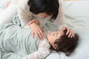 風邪を引いて寝込んでいる息子の看病をしているシングルマザー