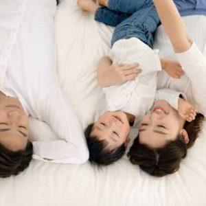 仲良く同じベッドで寝ている家族