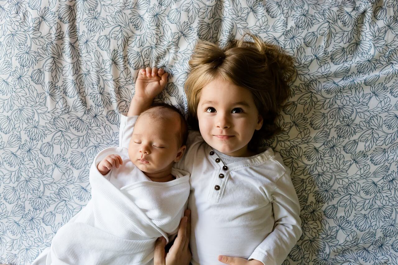 弟が産まれて嬉しくて一緒に寄り添って寝ている金髪の少年