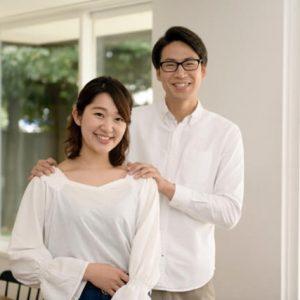 妻の肩に手を添えて笑顔の男性