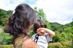 ぐずっている息子を抱っこする母親