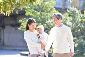 娘と孫と仲良く公園を散歩する男性