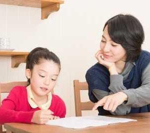 笑顔で仲良く子供の宿題を教える母親