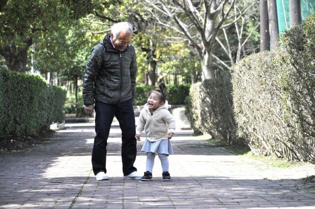 可愛いかわいい可愛すぎる孫と公園を散歩するおじいさん