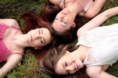 頭をつき合わせて仲良く寝そべる女性三人組