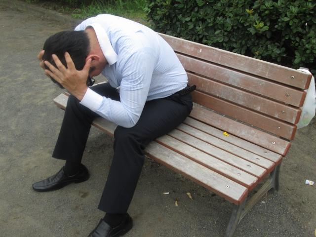 仕事でミスして公園で頭を抱えて落ち込む男性社員