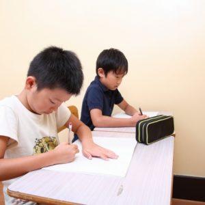 塾で友達と一緒に勉強している小学生の息子