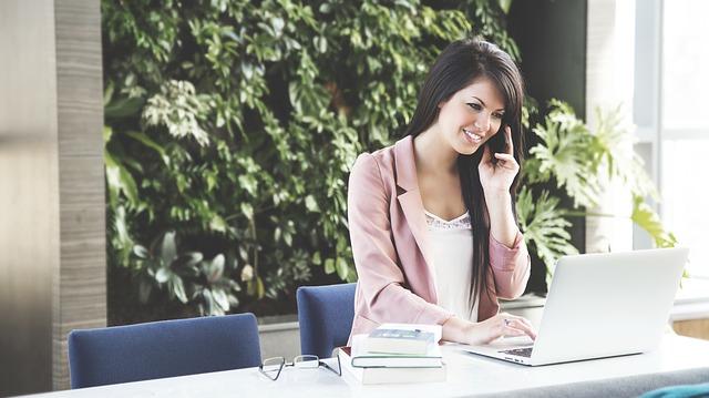出先でスマホから取引先に電話するピンクのジャケットを着た若い女性