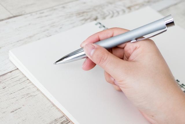 万年筆で母子手帳を書く女性