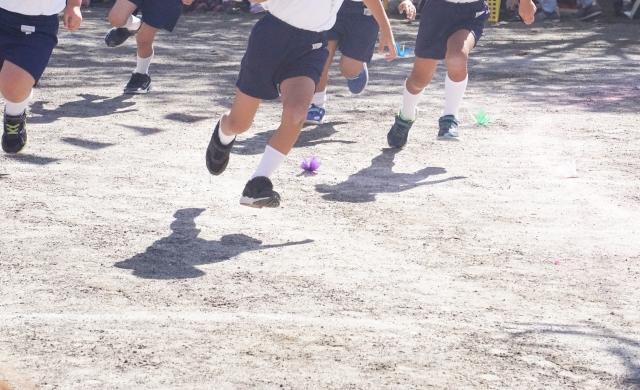 グラウンドを駆ける小学生の集団