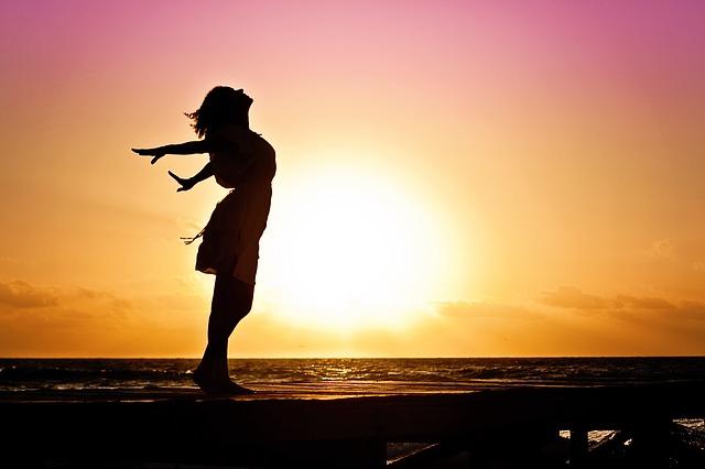 夕日に向かって生きる喜びを表現する女性