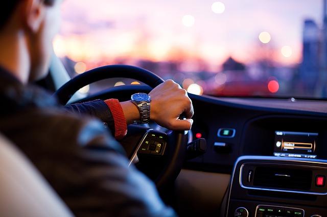 ラジオを聞きながら車を運転する紳士