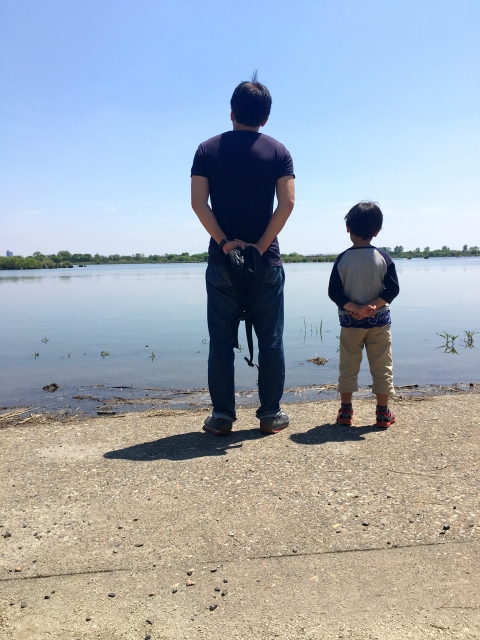 子離れできない親が息子と海を眺めている